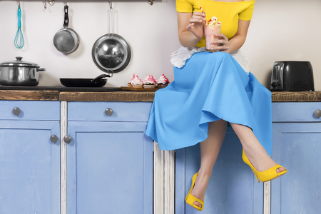 Photo pour Retro pin up girl woman female housewife wearing colorful top, skirt and white apron holding cooked sweet strawberry milkshake sitting in the kitchen with utensils and tray with cupcakes. - image libre de droit