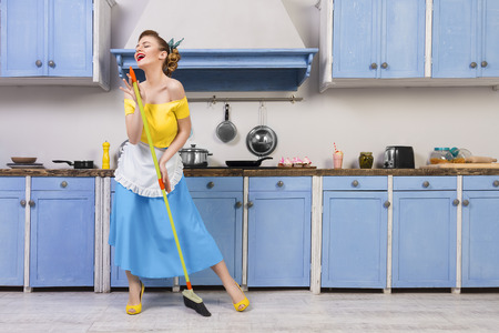 Photo pour Retro / pin up girl woman female / housewife wearing colorful top, skirt and white apron holding mop singing and cleaning floor in the kitchen with blue cabinets and utensils. Housework concept - image libre de droit
