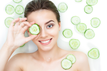 Photo pour Portrait of sexy beauty caucasian female woman with clean pure skin taking spa relaxing in bath with cucumber slices white soap shampoo water. Skin beauty health care concept. Body part bare shoulder - image libre de droit