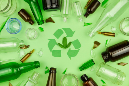 Foto de Green recycle sign symbol with glass trash garbage bottle, pills and tubes on green isolated background. Ecology recycle, environment issue, safe planet, refuse reuse recycle concept - Imagen libre de derechos