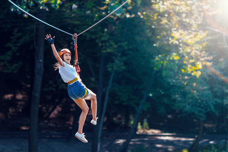 Photo pour Happy women girl female gliding climbing in extreme road trolley zipline in forest on carabiner safety link on tree to tree top rope adventure park. Family weekend children kids activities concept - image libre de droit