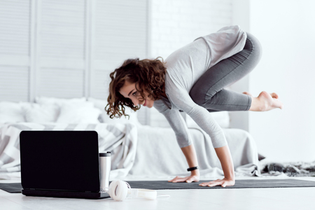 Foto de Young happy healthy fitness beautiful woman female doing bakasana yoga posture and workout on yoga mat opposite laptop with online master class at modern bedroom at home. Healthy lifestyle concept - Imagen libre de derechos