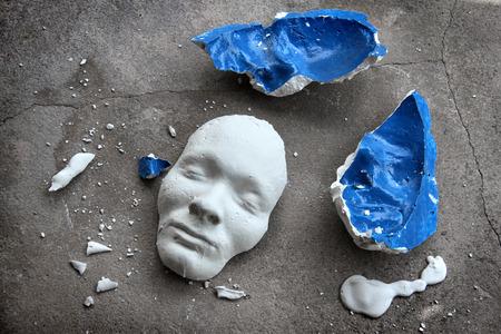 Foto de Plaster face mask between pieces of broken matt - Imagen libre de derechos
