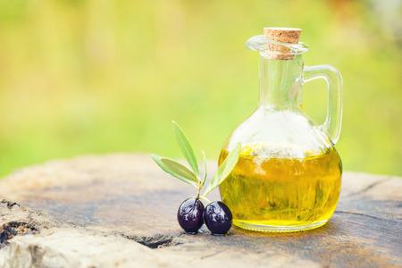 Foto de olives and oil in bottle on old textured wood - Imagen libre de derechos