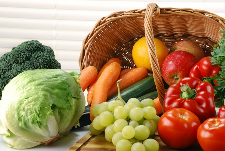 Composition with raw vegetables and wicker basket on kitchen table