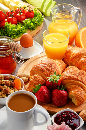 Photo for Breakfast consisting of croissants, coffee, fruits, orange juice, coffee and jam. Balanced diet. - Royalty Free Image