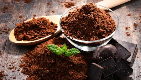 Foto de Composition with bowl of cocoa powder on wooden table. - Imagen libre de derechos