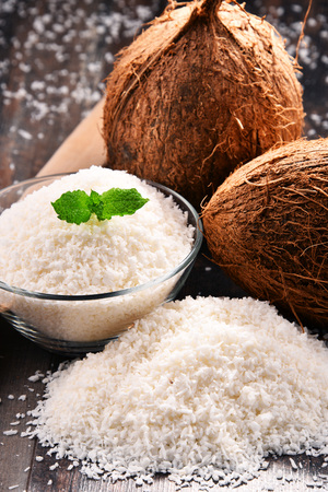 Photo pour Composition with bowl of shredded coconut and shells on wooden table - image libre de droit