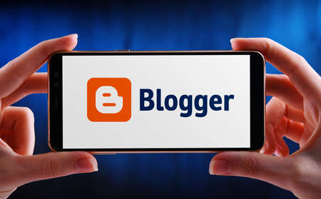 Foto de POZNAN, POL - MAY 21, 2020: Hands holding smartphone displaying logo of Blogger, a blog-publishing service that allows multi-user blogs with time-stamped entries - Imagen libre de derechos