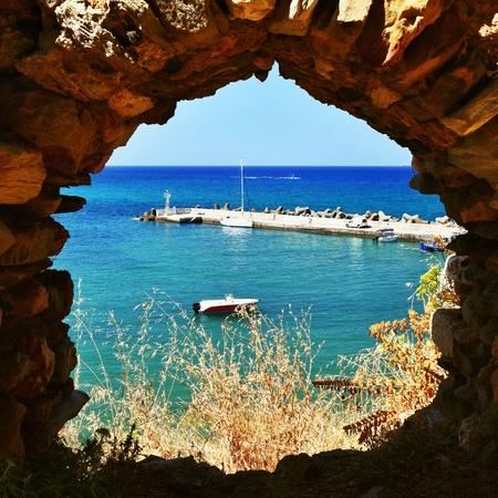 Foto de Traditional beautiful Greek village of Panormos on the island of Crete. Summer background for travel and holidays. - Imagen libre de derechos