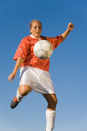 Photo pour Soccer Player Kicking Ball - image libre de droit