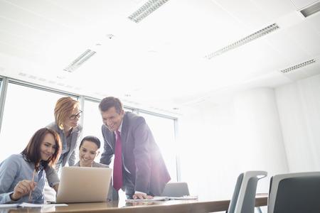 Foto de Businesspeople using laptop at conference table - Imagen libre de derechos