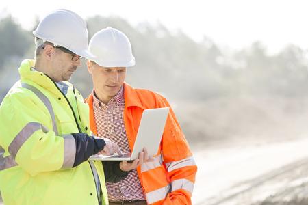 Photo pour Supervisors using laptop at construction site - image libre de droit