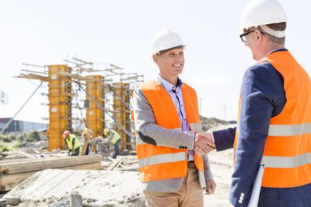 Photo pour Engineers shaking hands at construction site against clear sky - image libre de droit
