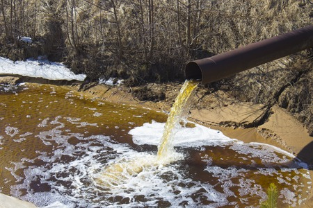 Foto de The Industrial Wastewater is Discharged from the Pipe - Imagen libre de derechos