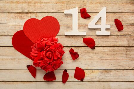 Photo pour Wooden background with petals, flowers, hearts and wooden numbers of dated 14 February. The concept of Valentine Day. - image libre de droit