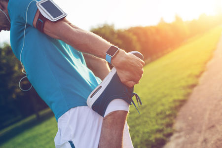Photo pour Athlete with armband doing warming stretching outdoors in park - image libre de droit