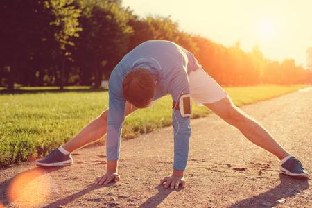 Photo pour Young athlete doing warming before workout in the park, lens flares - image libre de droit