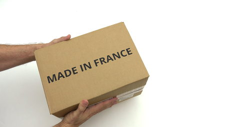 Photo pour Man holds parcel with MADE IN FRANCE text on it - image libre de droit