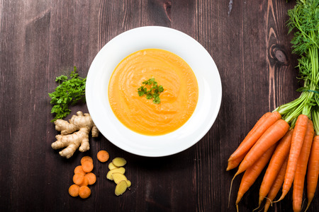 Photo pour Fresh carrot ginger soup with ingredients on background - image libre de droit