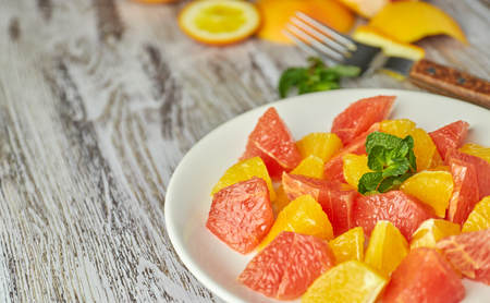 Photo for Orange-grapefruit citrus salad on a shabby wooden table. copy space. summer vitamin - Royalty Free Image