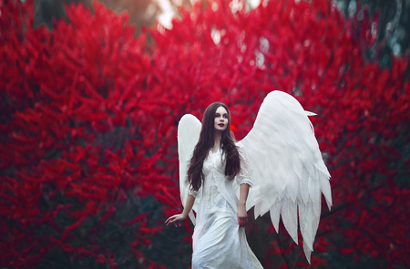 Photo for Art photo of a Angelic beautiful woman. A girl with angel wings and a white dress near blood-red trees. - Royalty Free Image