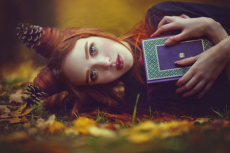 Photo for Portrait of a beautiful red-haired girl with an unusual hairdo with a book in the autumn fairy forest. A fabulous autumn photo shoot. - Royalty Free Image