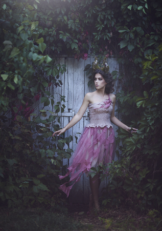 Photo for Girl enchanted Princess with horns. Girl Mystical fairy creature fawn in shabby clothes near the old door. Halloween concept ideas. - Royalty Free Image