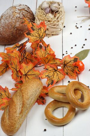 Autumn still life with a bakery on a board on a white wooden table, near orange maple leaves.