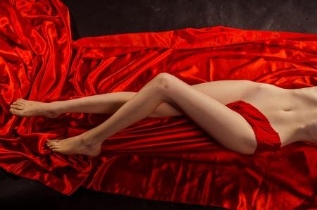 Photo pour Pretty legs with red silk and black background. - image libre de droit