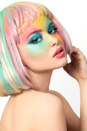 Photo pour Portrait of young woman with funny rainbow coloured make-up touching her hair - image libre de droit