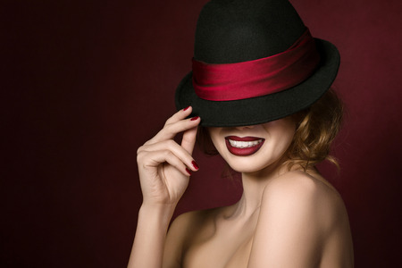 Photo for Portrait of young beautiful actress holding black hat with red ribbon over dark red background - Royalty Free Image