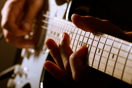 Photo for Hands of man playing electric guitar. Low key photo. - Royalty Free Image