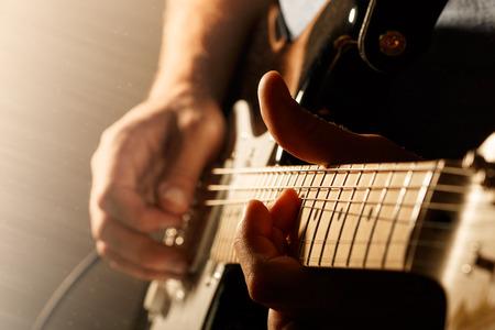 Photo pour Hands of man playing electric guitar. Bend technique. Low key photo. - image libre de droit