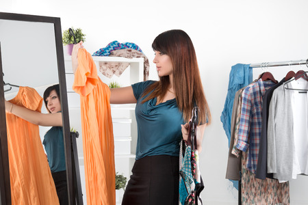 Foto de Beautiful young woman standing between mirror and rack with clothes making chioce - Imagen libre de derechos