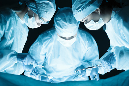Foto de Medical team performing operation. Group of surgeon at work in operating theatre tonned in blue - Imagen libre de derechos