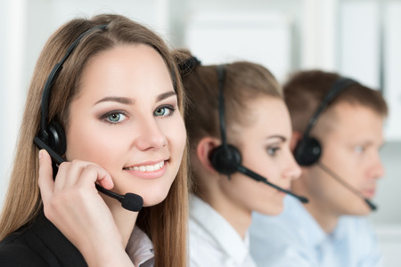 Foto de Portrait of call center worker accompanied by her team. Smiling customer support operator at work. Help and support concept - Imagen libre de derechos