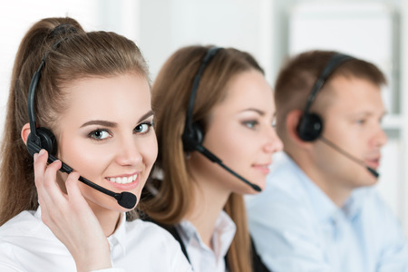 Photo pour Portrait of call center worker accompanied by her team. Smiling customer support operator at work. Help and support concept - image libre de droit