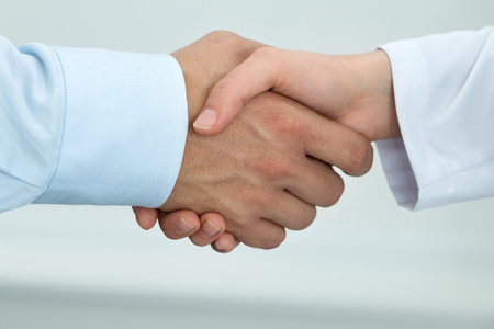 Photo for Female medicine doctor shaking hands with male patient. Partnership, trust and medical ethics concept. Handshake with satisfied client. Healthcare and medical concept - Royalty Free Image