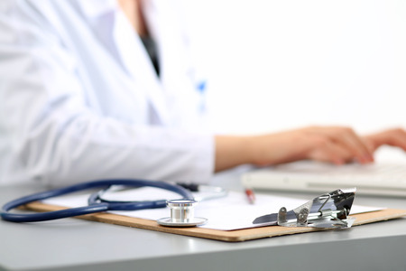 Foto de Medicine doctor's working place. Focus on stethoscope, doctor's hands typing something on background. Healthcare and medical concept. Copyspace - Imagen libre de derechos