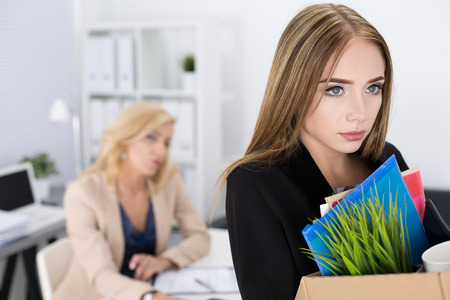 Photo pour Boss dismissing an employee. Dejected fired office worker carrying a box full of belongings. Getting fired concept. - image libre de droit