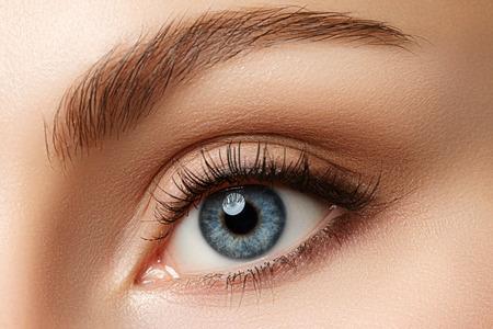 Foto de Close up view of beautiful blue female eye. Good vision, contact lenses, trust or observation concept - Imagen libre de derechos