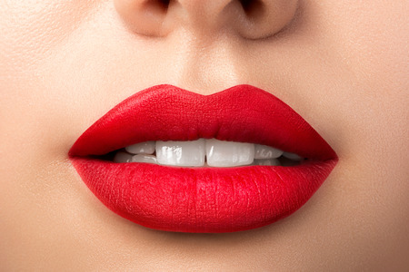 Photo pour Close up view of beautiful woman lips with red matt lipstick. Open mouth with white teeth. Cosmetology, drugstore or fashion makeup concept. Beauty studio shot. Passionate kiss - image libre de droit