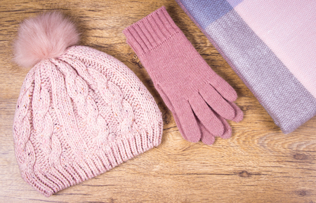 Foto de Warm winter knitted clothes: hat, scarf and gloves on a wooden background. Close Up. - Imagen libre de derechos