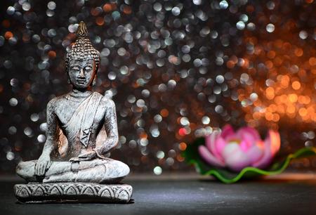 Foto de Zen Buddha statue and a lotus flower on a bright shiny glitter background with bokeh - Imagen libre de derechos