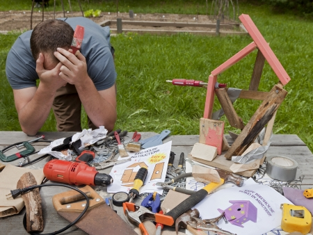 Photo for A man is frustrated and angry at building a bad birdhouse  - Royalty Free Image