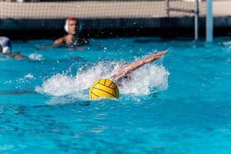 Photo for Floating water polo ball and emerging arm from submerged player while goalie looks on during competition match. - Royalty Free Image