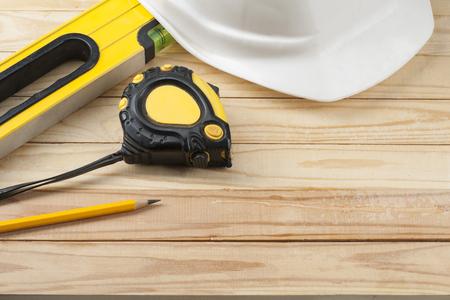 Foto de Construction tools and white helmet on wooden background .Copy space for text. - Imagen libre de derechos