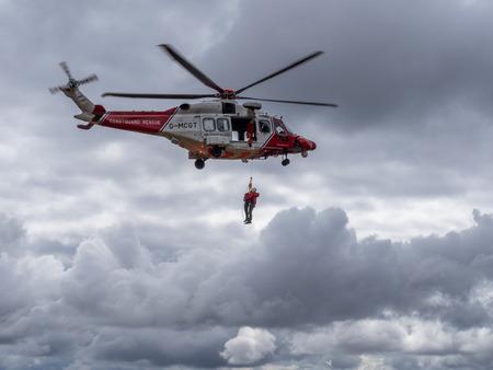 Foto de Ben Arthur, The Cobbler, Scotland 29th April 2018. A coastguard helicopter droping off mountain rescue team members to help an injured walker who was later carried off the hill. - Imagen libre de derechos