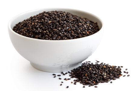 Photo pour Black sesame seeds  in white ceramic bowl isolated on white. Spilled seeds. - image libre de droit